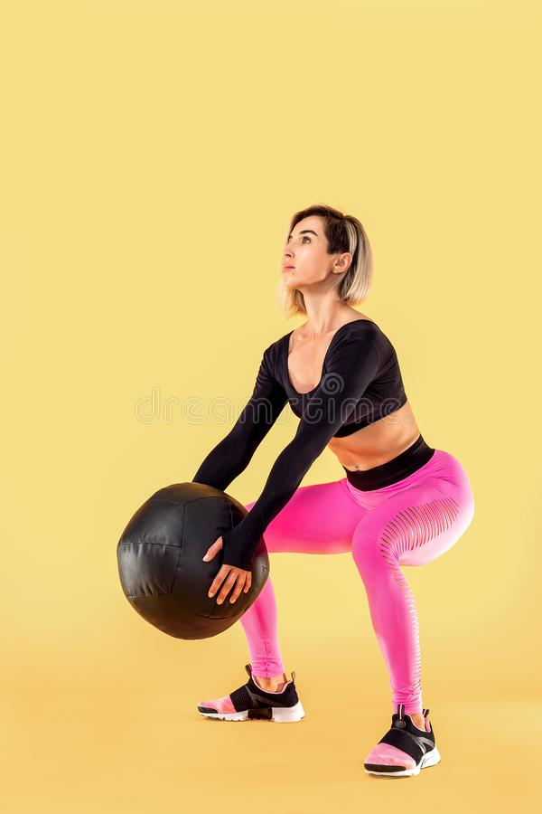 Strong woman workout with med ball. Photo of sporty latin woman in fashionable sportswear on yellow background. Strength and motivation royalty free stock photography
