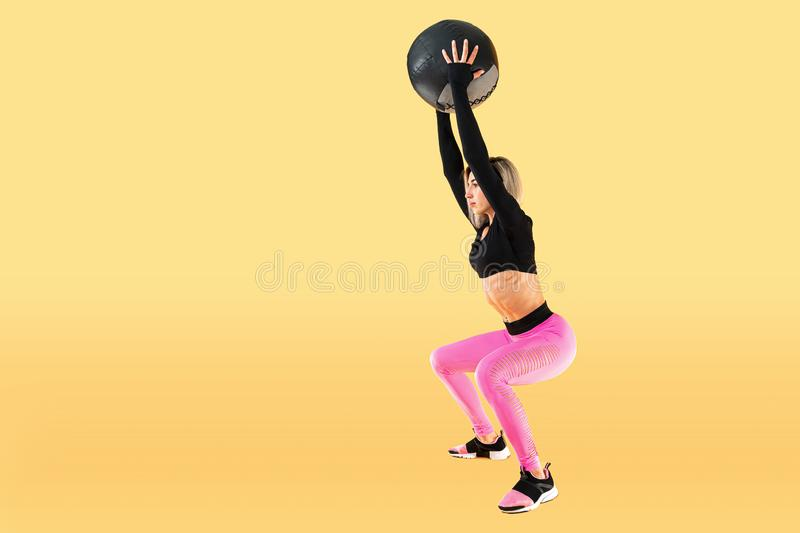 Strong woman workout with med ball. Photo of sporty latin woman in fashionable sportswear on yellow background. Strength and motivation stock photo