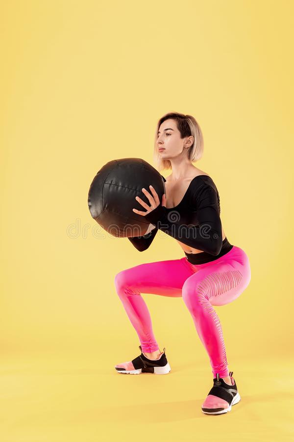 Strong woman workout with med ball. Photo of sporty latin woman in fashionable sportswear on yellow background. Strength and motivation stock photography
