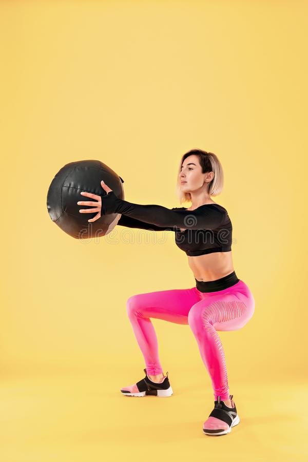 Strong woman workout with med ball. Photo of sporty latin woman in fashionable sportswear on yellow background. Strength and motivation stock image