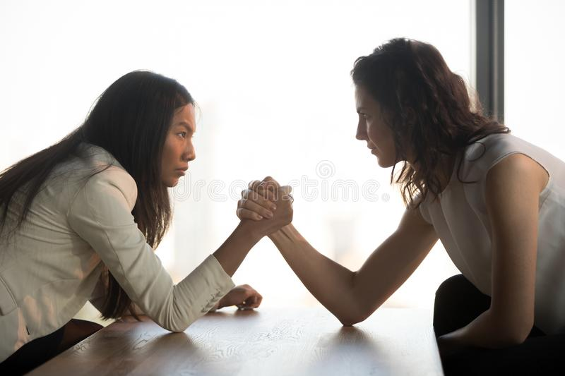 Strong women arm wrestle at work struggle for leadership. Two multiracial millennial women sit opposite look in eyes arm wrestle to get leadership at work royalty free stock photography