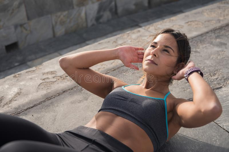 Strong young brunette doing fitness training. Outside in the sunlight wearing tights and grey top and a watch around her wrist stock photos