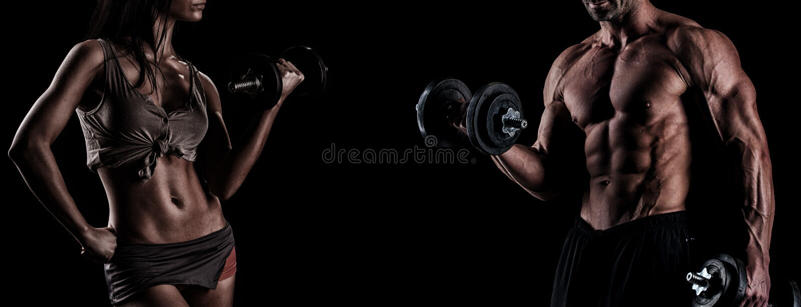 Strong young couple working out with dumbbells. Shot in studio o stock images