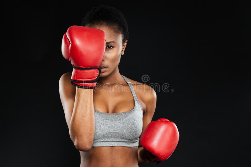 Strong young fitness woman covered her face with boxing gloves stock images
