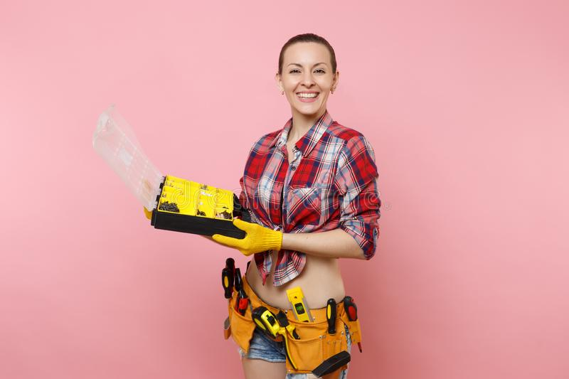Strong young handyman woman in plaid shirt, denim shorts, kit tools belt full of different instruments holding toolbox royalty free stock images