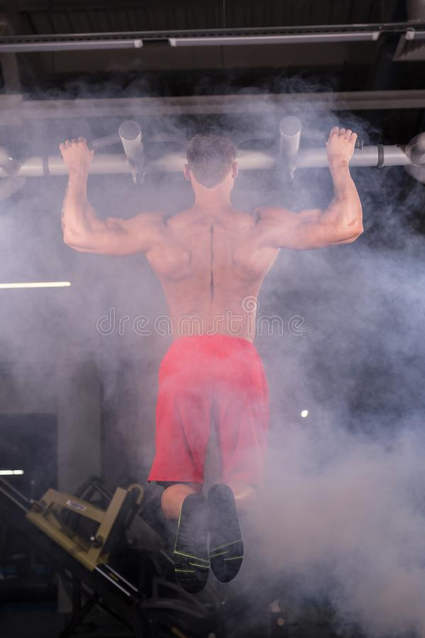 Strong young man doing pull up exercise on horizontal bar in gym stock photo