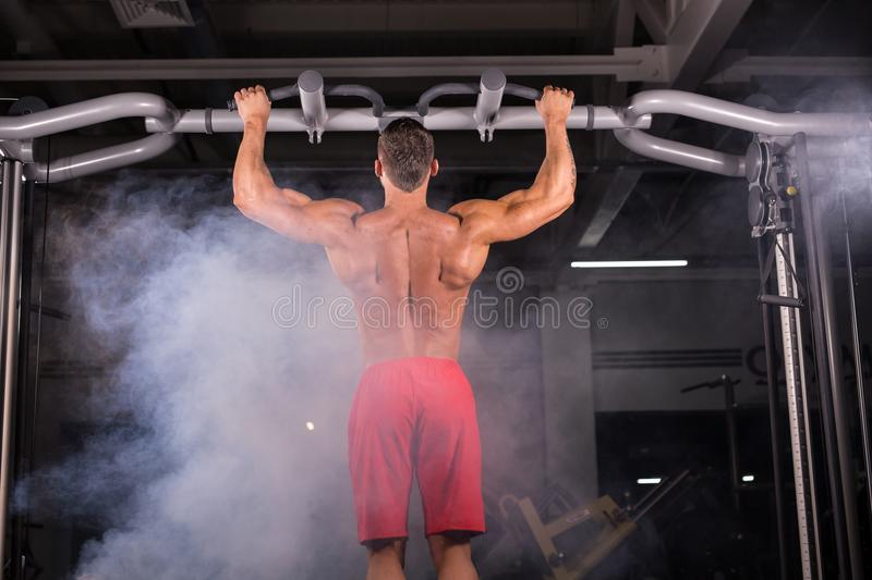 Strong young man doing pull up exercise on horizontal bar in gym royalty free stock photos
