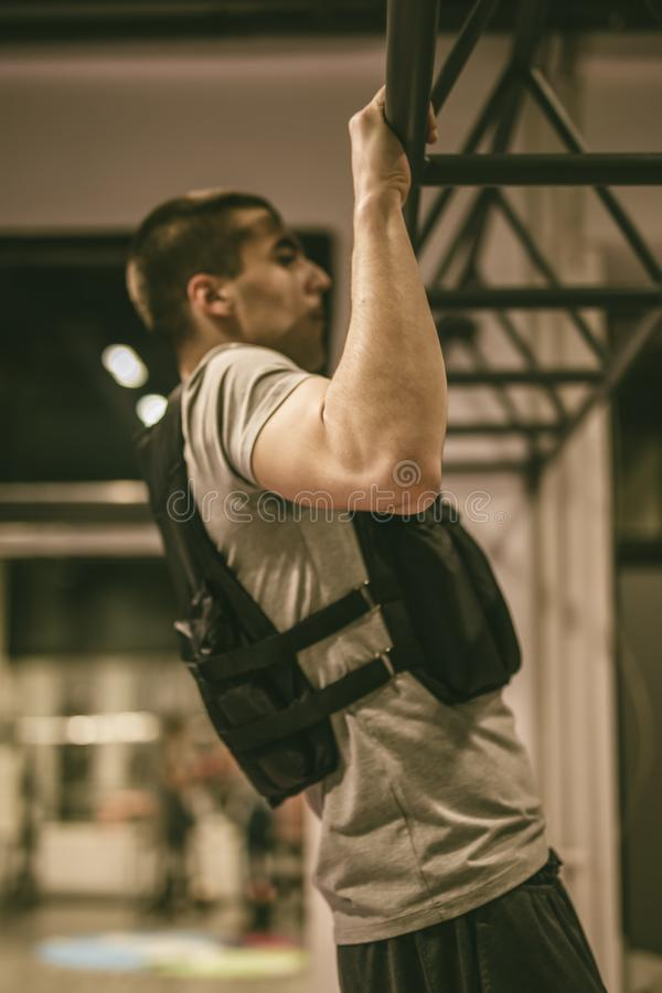 Young man doing pull ups in the gym. Strong young man doing pull ups in the gym stock photo
