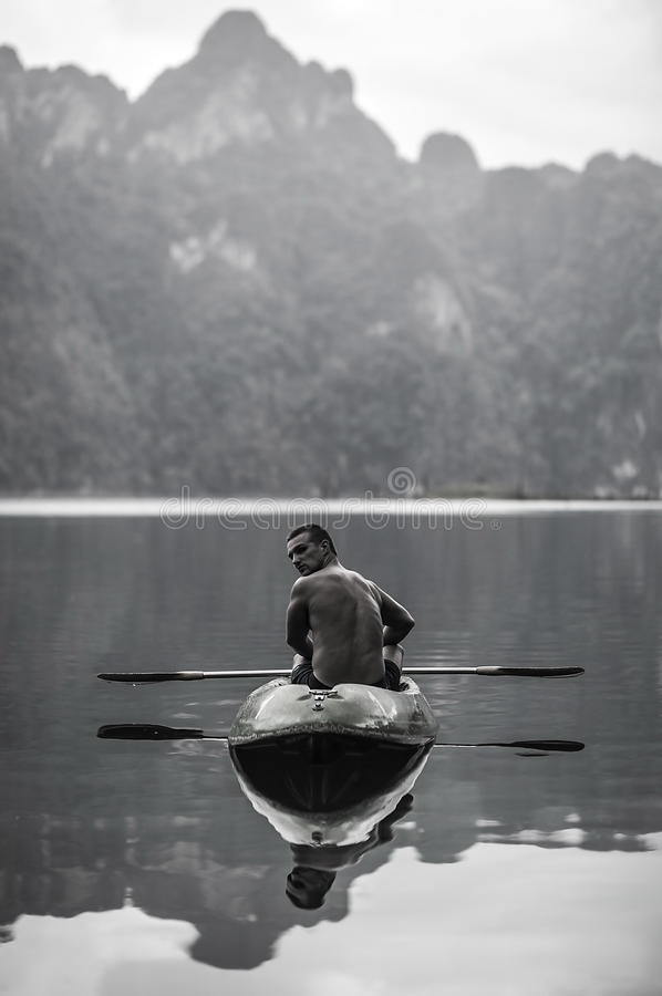 Strong young man in kayak on the picturesque lake in Thailand. royalty free stock image