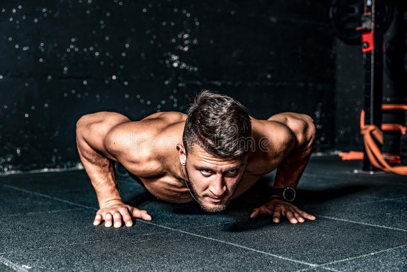 Strong young toned muscular fitness man push ups workout training on the gym floor. Push ups workout, Strong young toned muscular fitness man push ups workout stock photography