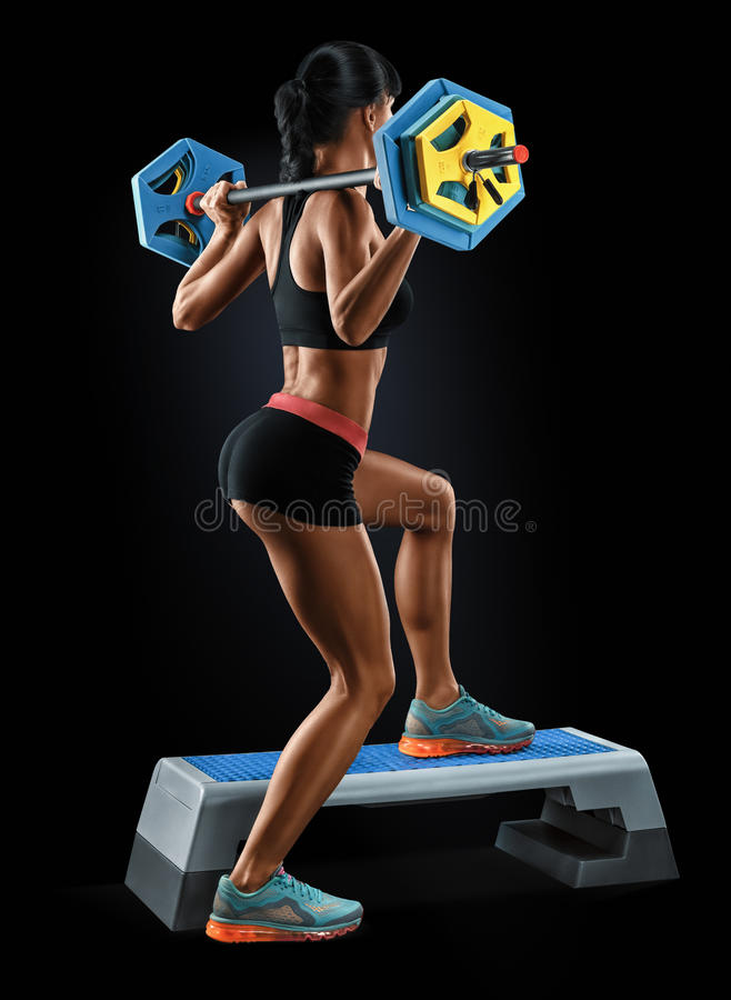 Strong young woman with athletic body doing exercises with barbell royalty free stock photography