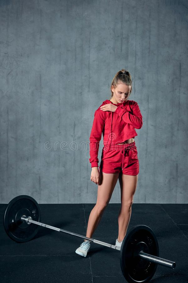 Strong young woman with beautiful athletic body doing exercises with barbell. stock photography