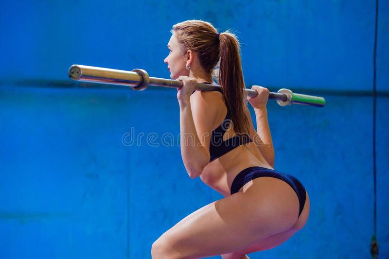 Strong young woman with beautiful athletic body doing exercises with barbell. Fitness, bodybuilding. Health care. royalty free stock images