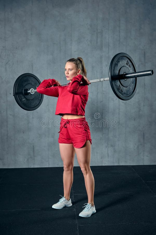 Strong young woman with beautiful athletic body doing exercises with barbell. royalty free stock photography