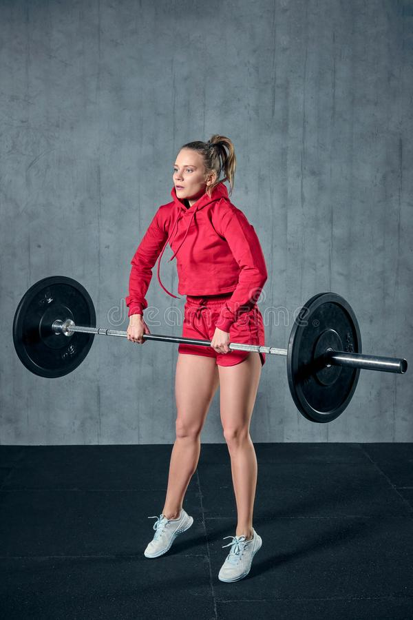 Strong young woman with beautiful athletic body doing exercises with barbell. stock images