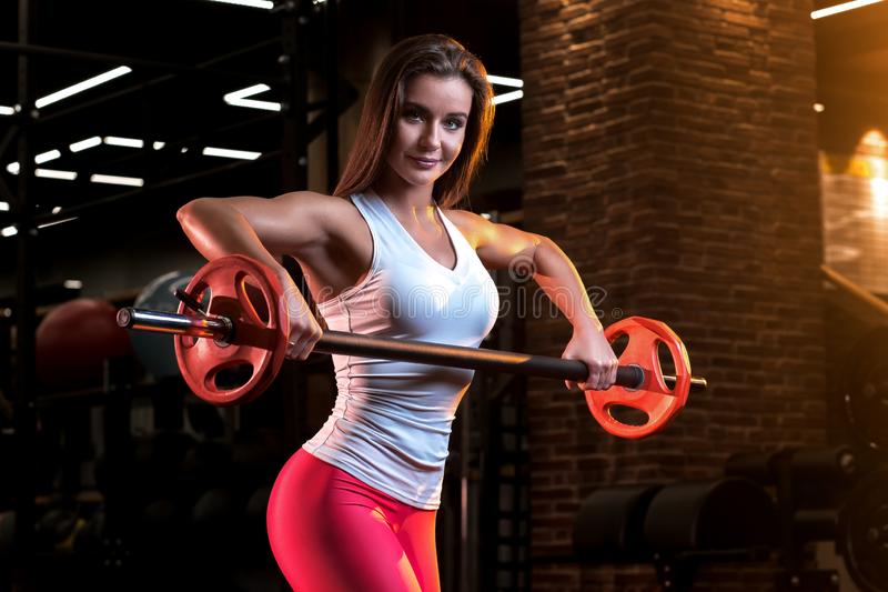 Strong young woman with beautiful athletic body doing exercises with barbell. stock image