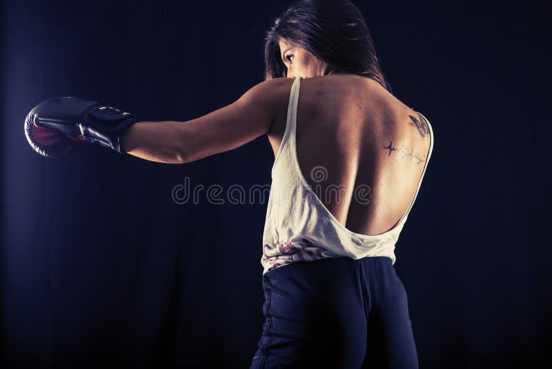 Strong young woman boxing performing a jab kick stock photo