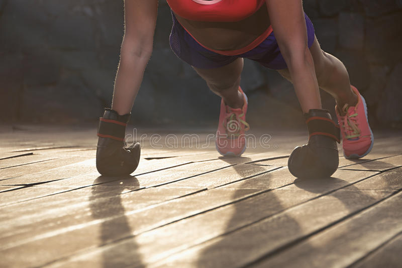 Strong young woman doing push-ups royalty free stock photography