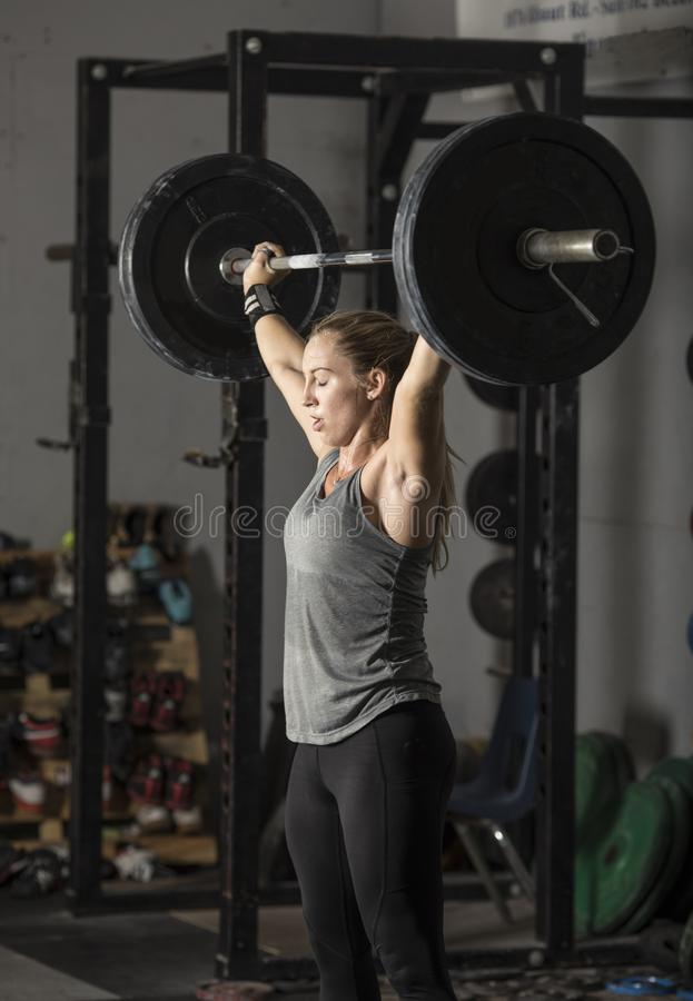 Strong young woman lifting heavy weights over her head royalty free stock photos