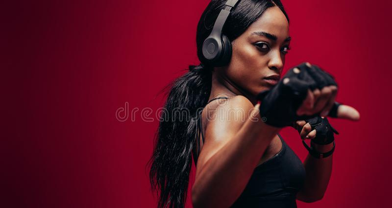 Strong young woman practising boxing stock images
