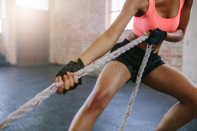 Strong young woman pulling rope at a gym stock photography