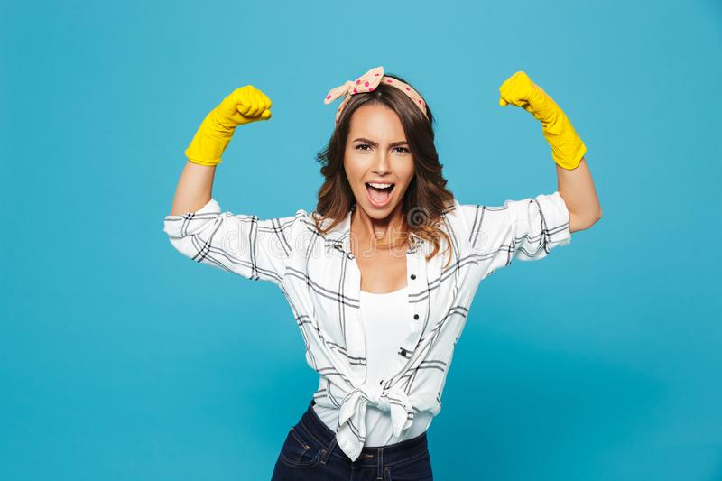 Strong young woman 20s raising arms and showing biceps while wearing yellow rubber gloves for hands protection during cleaning, i stock photo