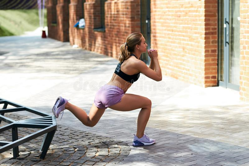 Strong young woman stretching her legs royalty free stock photo