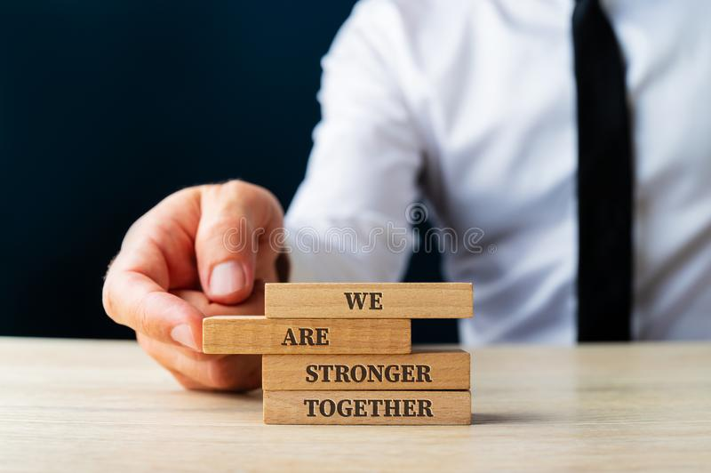 We are stronger together sign. On wooden pegs being stacked by a business executive in a conceptual image. Over dark blue background stock image