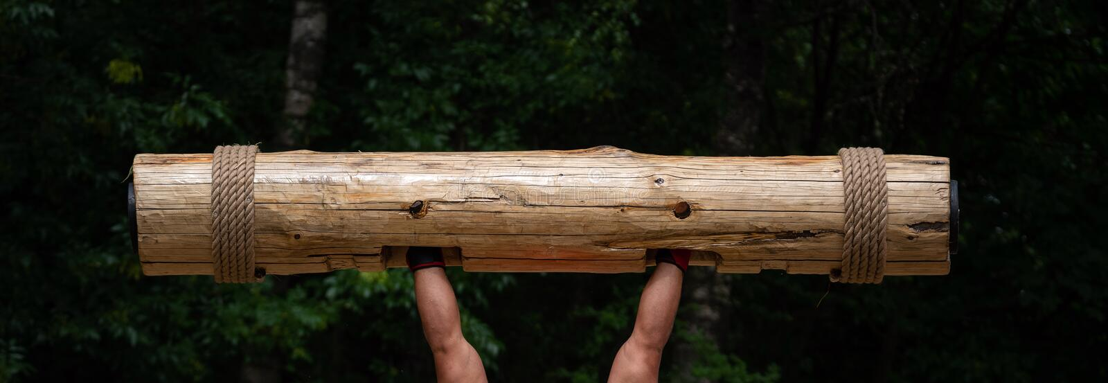 Strongest man in the world competition. Muscular hands lifting up heavy wooden trunk. Giant, mighty man lifting wood log at. Competition stock photos