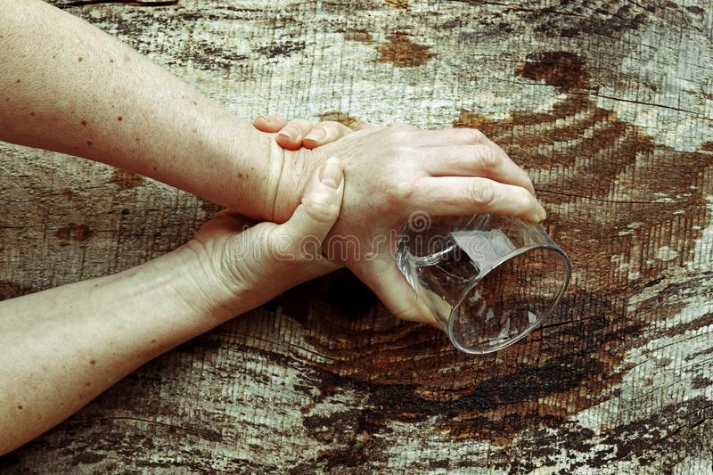 Strongly trembling hands of an older woman stock image