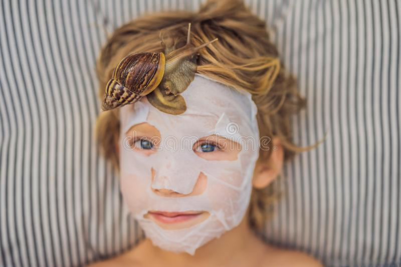 Strongly younger from the mask with snail mucus. A child in a mask for the face with a snail. Snail crawling on a face. Mask. SPA for all stock images