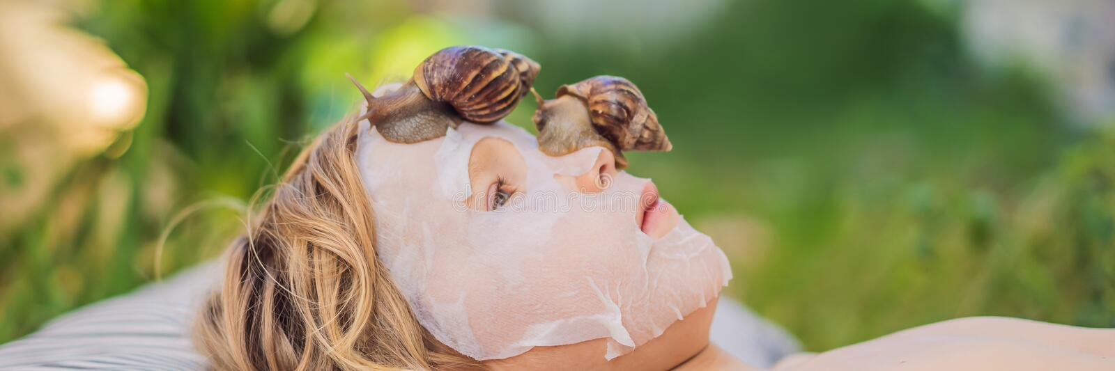 Strongly younger from the mask with snail mucus. A child in a mask for the face with a snail. Snail crawling on a face. Mask. SPA for all. BANNER, LONG FORMAT royalty free stock image