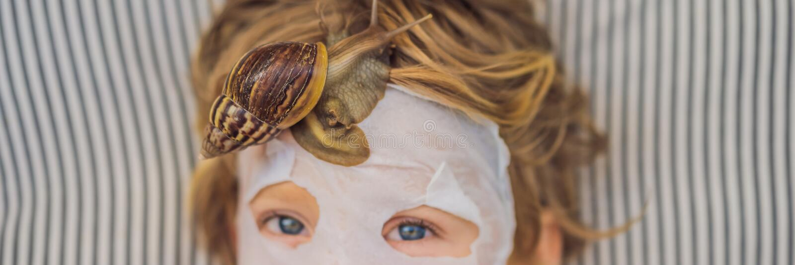 Strongly younger from the mask with snail mucus. A child in a mask for the face with a snail. Snail crawling on a face. Mask. SPA for all. BANNER, LONG FORMAT royalty free stock photography