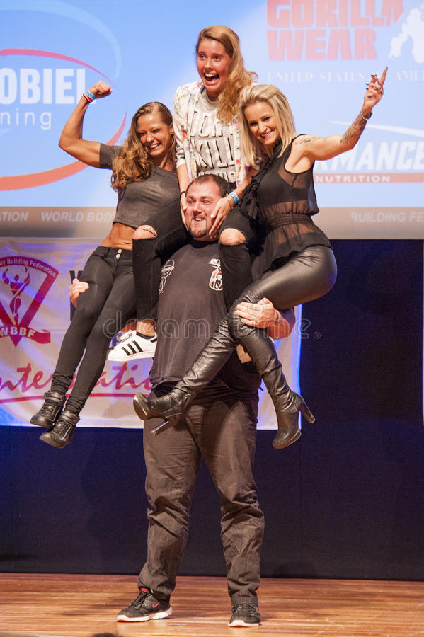 Strongman Jimmy Laureys de liftenmeisjes van België op stadium royalty-vrije stock afbeeldingen
