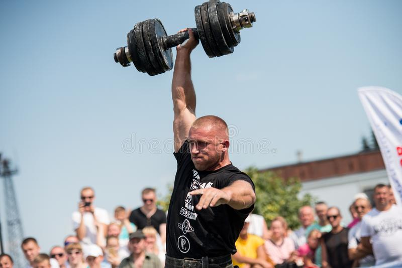 Strongman raises heavy dumbbell with one hand at competitions, Ukraine, 2017 royalty free stock photography