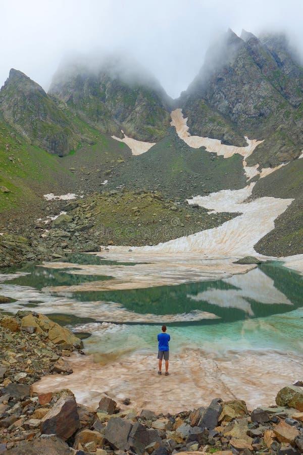 Stronniczo marznący Didighali jezioro z młodym człowiekiem i przełęcz w tle w Kaukaz górach na wycieczkuje śladzie Si zdjęcie stock