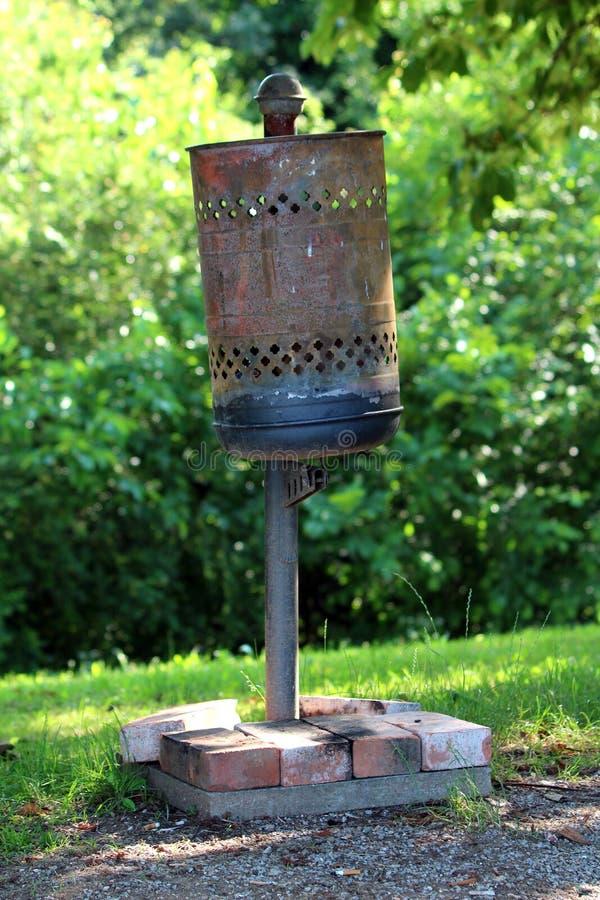 Stronniczo rdzewiejący starego obdrapanego metalu jawny kubeł na śmieci trzymał na miejscu z betonową podstawą zakrywającą z mały zdjęcie royalty free