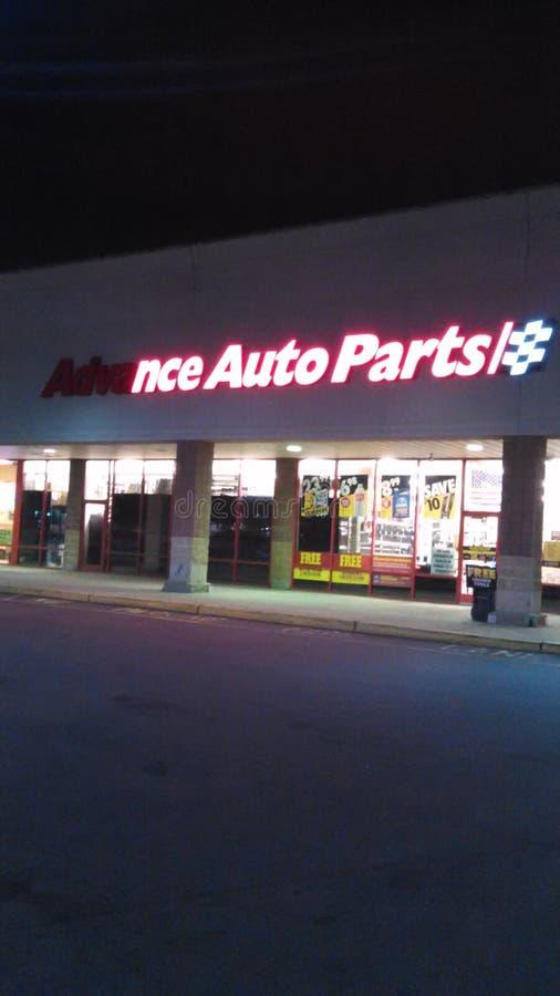 Stronniczo zaświecający Zaliczkowy Auto część przodu sklepu znak z logo przy nocą NJ, usa obraz stock