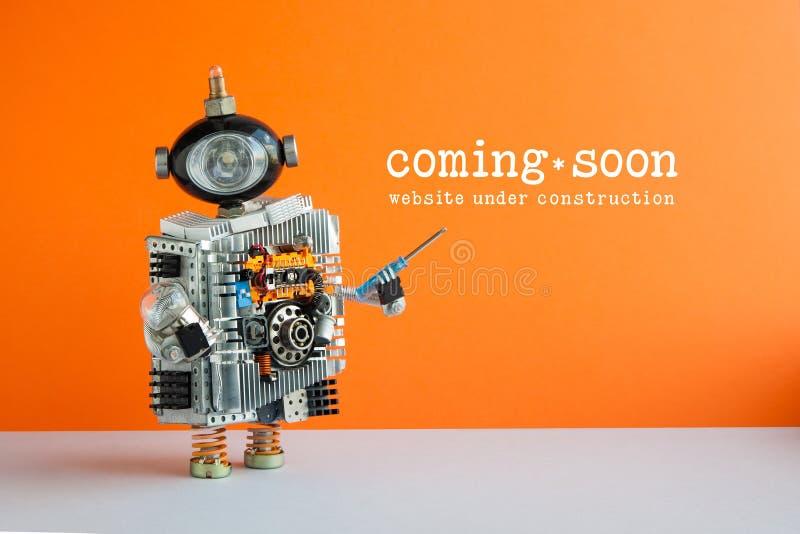 Strony internetowej przybycia Wkrótce w budowie strona Zabawkarski robot z śrubokrętem i żarówką Pomarańcze ścienna szara podłoga fotografia stock