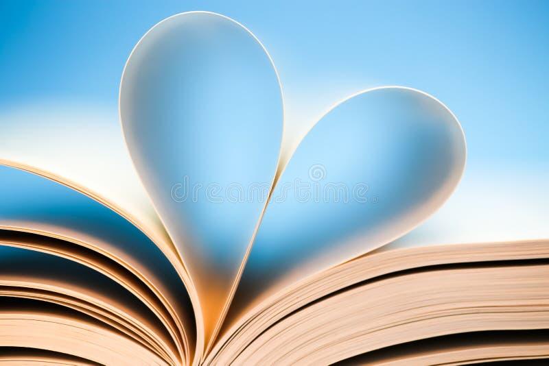 Strony książek na niebieskim tle, błyszczące serce utworzone przez książkę zdjęcia royalty free