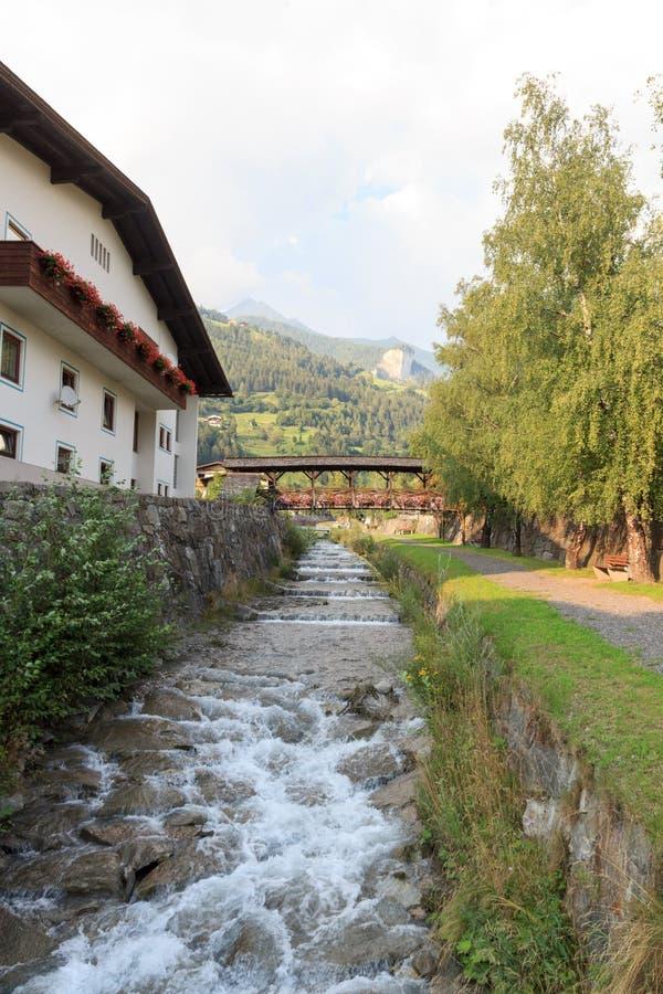 Stroom Bretterwandbach met brug in Matrei, Oostenrijk stock afbeelding