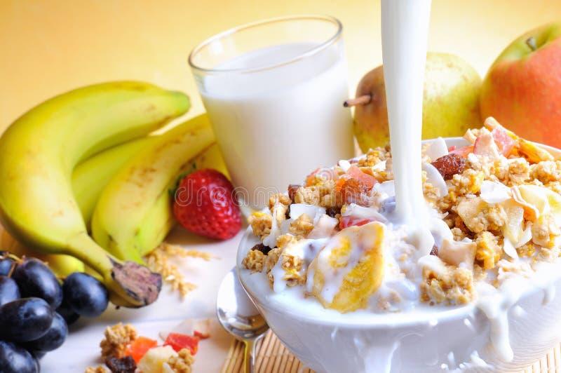 Stroom die van melk in een kom graangewas en vruchten vallen royalty-vrije stock fotografie