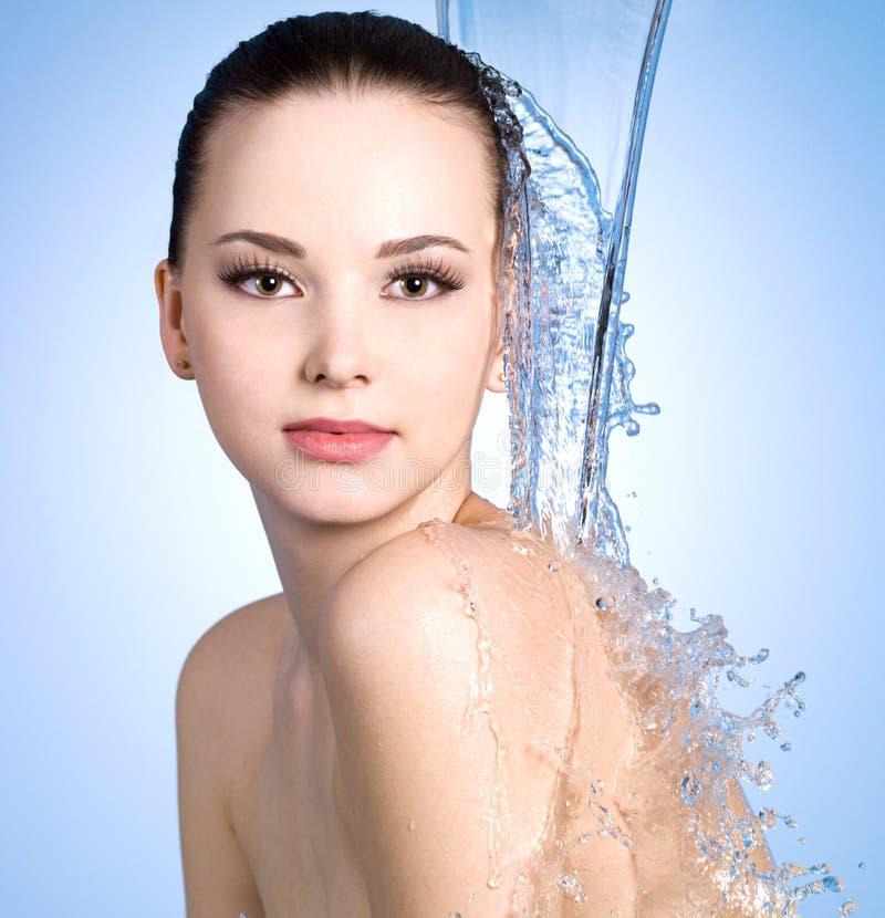 Stroom die van water op het lichaam van vrouw valt stock fotografie
