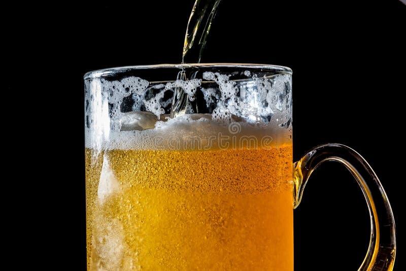 Stroom van bier die gietend in een glas met bier en schuim zijn die op zwarte achtergrond, close-uptextuur wordt geïsoleerd stock foto's