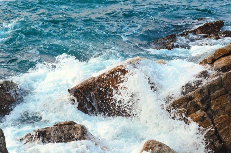 Stroom van waterneerstortingen bij rotsachtig strand, woedende overzees Zeewater met schuim, golf en strand stock fotografie
