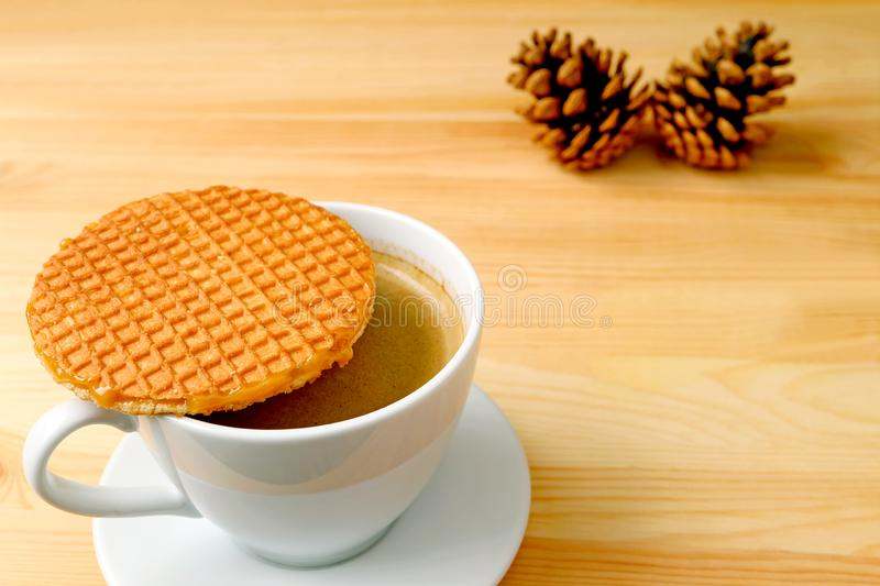Stroopwafel Dutch Cookie Placed on Hot Coffee Cup Served on Wooden Table with Blurred Natural Pine Cones in Background stock photo