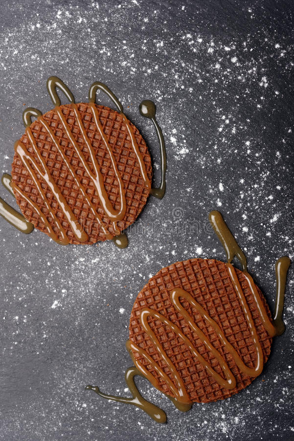 Stroopwafels with caramel sauce. On a slate surface royalty free stock image