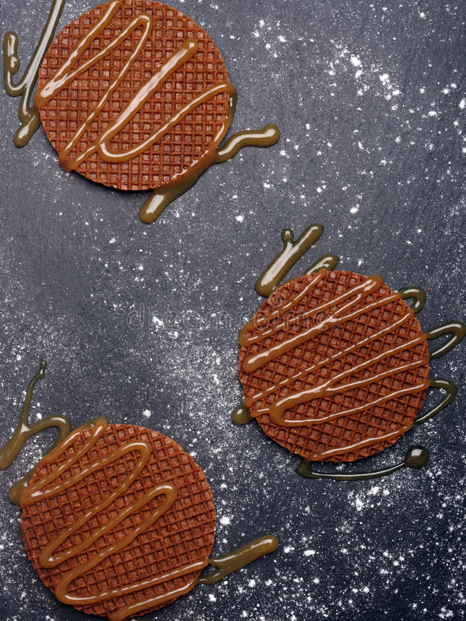 Stroopwafels with caramel sauce. On a slate surface stock image