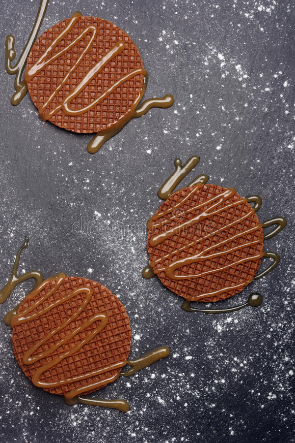 Stroopwafels with caramel sauce. On a slate surface stock images