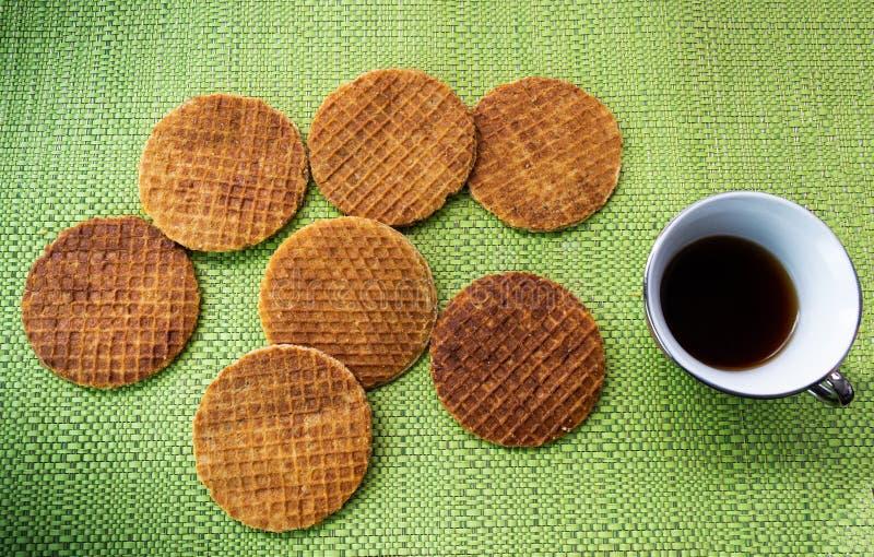 Stroopwafels met koffie op een lijst met groen tafelkleed stock foto